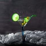 Vetro del cocktail sulla tavola Olive, rosmarini e calce in un g Immagine Stock Libera da Diritti