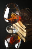 Vetro del cognac e dei libri fotografia stock