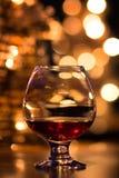 Vetro del cognac sui precedenti delle luci festive Fotografia Stock Libera da Diritti