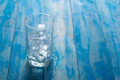 Vetro del cubetto di ghiaccio sul fondo di legno blu della tavola Immagine Stock Libera da Diritti