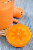Vetro del frullato del cachi con il succo di carota Fotografie Stock Libere da Diritti