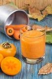 Vetro del frullato del cachi con la cannella aromatizzata del succo di carota, decorato dagli ingredienti e dalle foglie cadute s Immagine Stock Libera da Diritti
