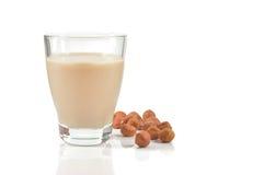 Vetro del latte o della bevanda della nocciola su bianco Fotografia Stock