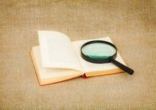 Vetro del magnifier e del vecchio libro su tela di canapa Immagine Stock