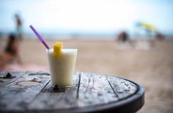 Vetro del pinacolada sulla tavola sulla spiaggia fotografia stock