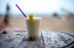 Vetro del pinacolada sulla tavola sulla spiaggia fotografie stock
