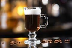 Vetro del primo piano del cocktail dell'irish coffee al contatore luminoso della barra immagini stock libere da diritti