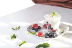 Vetro del primo piano del ` di yogurt con le bacche e la menta fresche sul piatto bianco Immagini Stock