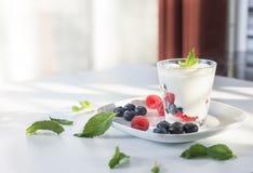 Vetro del primo piano di yogurt con le bacche e la menta fresche sul piatto bianco immagine stock