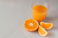 Vetro del succo d'arancia ed arance fresche Immagini Stock