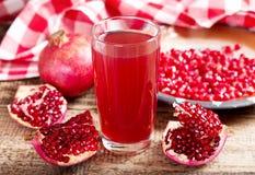 Vetro del succo del melograno con la frutta fresca fotografie stock
