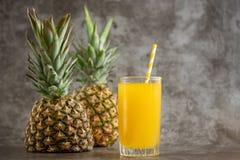 Vetro del succo di ananas con la frutta fresca su bacground grigio fotografia stock libera da diritti