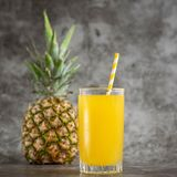 Vetro del succo di ananas con la frutta fresca su bacground grigio immagini stock libere da diritti