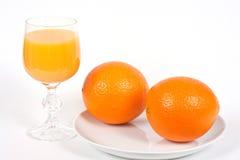 Vetro del succo di arancia e di due aranci su una zolla Fotografia Stock