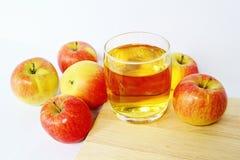 Vetro del succo di mele circondato con le mele fresche Immagine Stock