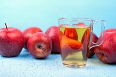 Vetro del succo di mele e delle mele rosse su fondo di legno Fotografie Stock