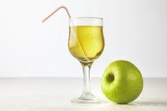 Vetro del succo di mele su bianco Fotografia Stock