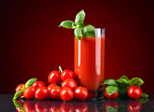 Vetro del succo di pomodoro con i piccoli pomodori rossi fotografie stock libere da diritti