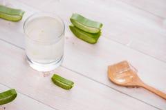 Vetro del succo di vera dell'aloe con le fette su una tavola di legno Fotografia Stock