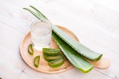 Vetro del succo di vera dell'aloe con le foglie fresche su una tavola di legno Fotografie Stock
