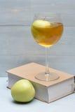 Vetro del succo e del libro di mele Fotografia Stock