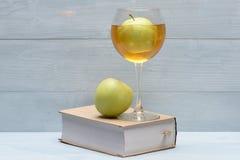 Vetro del succo e del libro di mele Immagine Stock
