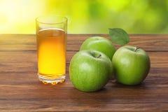Vetro del succo e delle mele di mele su legno Immagine Stock