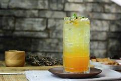 Vetro del succo del frutto della passione sul sottobicchiere di vetro rotondo Fotografia Stock