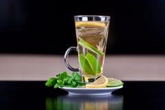 Vetro del tè con le fette della calce e della bustina di tè Fotografia Stock