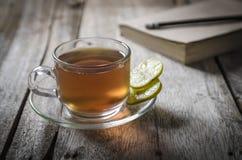 Vetro del tè di raffreddamento del limone sulla tavola di legno con il libro e la matita Immagine Stock
