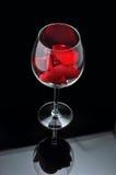 Vetro del vino rosso con i petali Immagine Stock