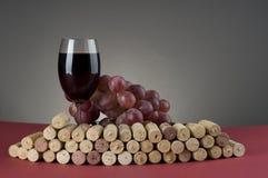 Vetro del vino rosso con l'uva ed i sugheri. immagini stock