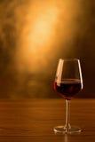 Vetro del vino rosso sulla tavola di legno e sul fondo dorato Immagini Stock