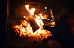 Vetro del whiskey con il fondo del falò immagini stock