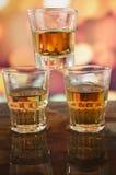 Vetro del whiskey del rum sopra le luci defocused immagine stock libera da diritti