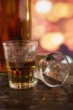 Vetro del whiskey del rum sopra le luci defocused Immagini Stock