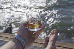 Vetro del whiskey della tenuta dell'uomo dal mare Fotografie Stock