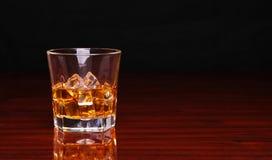 Vetro del whiskey scozzese dell'alcool con il cubetto di ghiaccio sulla tavola di legno Immagine Stock Libera da Diritti