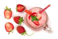 Vetro del yogurt della fragola con le foglie di menta isolate su fondo bianco Vista superiore Fotografia Stock