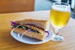 Vetro dell'hamburger rassodato della birra con l'alimento fritto della via del panino del pesce immagini stock libere da diritti