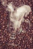 Vetro dell'irish coffee con fumo in chicchi di caffè fotografia stock libera da diritti
