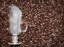 Vetro dell'irish coffee con fumo in chicchi di caffè fotografia stock