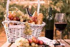 Vetro dell'uva del vino rosso e del canestro di picnic sulla tavola nel campo Fotografie Stock