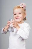 Vetro della holding della bambina di acqua fotografie stock libere da diritti
