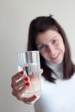 Vetro della holding della giovane donna di acqua Fotografia Stock