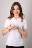 Vetro della holding della ragazza di latte Fine in su Priorità bassa bianca Fotografia Stock