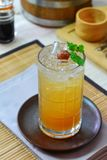 Vetro della prugna cinese sul sottobicchiere di vetro rotondo, biancheria da tavola Immagine Stock