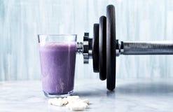 Vetro della scossa della proteina con latte e mirtilli, capsule dell'Beta-alanina e una testa di legno nel fondo Nutritio di cult fotografia stock libera da diritti