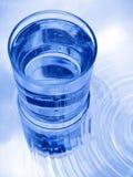 Vetro di acqua in azzurro immagini stock