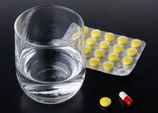 Vetro di acqua con le pillole Fotografia Stock